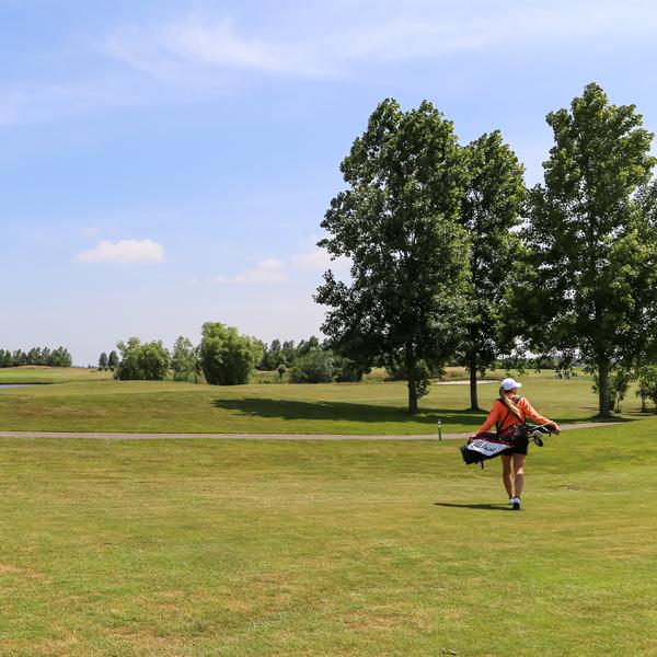 mevrouw met pet op loopt met golfclubs over golfbaan