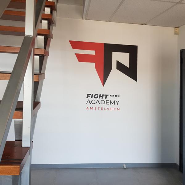 Muursticker van rood-zwart logo op witte muur in de sportschool