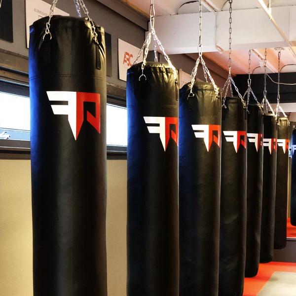 Zwarte punching bags in de vechtsportschool voorzien van krachtig nieuw logo