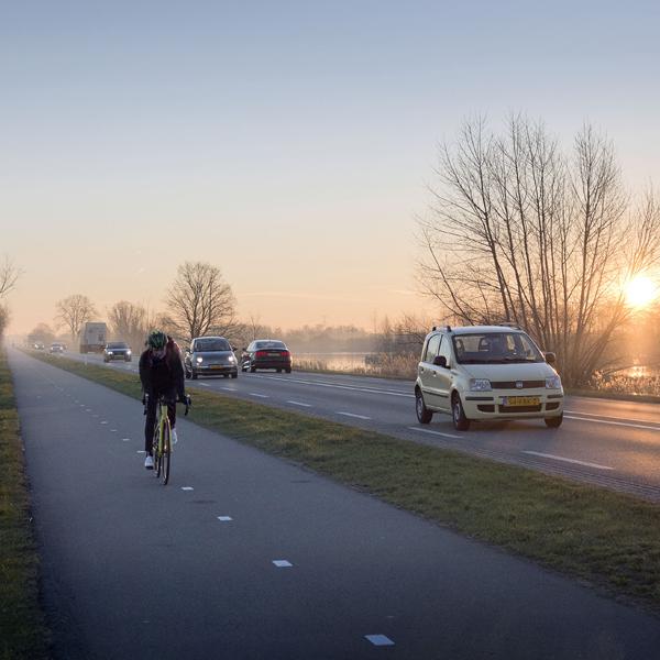 Sfeerbeeld met fietser en auto in De Ronde Venen - Meer fotografie vind je op werkenvoorderondevenen.nl