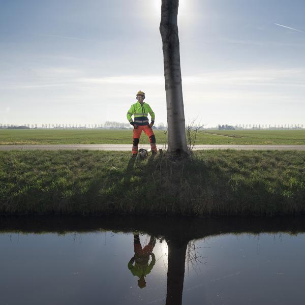 Groenmedewerker naast een boom - Aan het werk voor gemeente De Ronde Venen? Bekijk werkenvoorderondevenen.nl