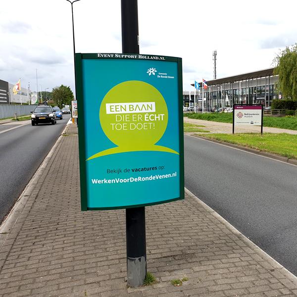 Blauw groene poster om een lantaarnpaal - Wervende campagne voor de gemeente